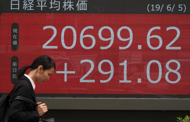 A woman walks past an electronic stock board showing Japan's Nikkei 225 index at a securities firm in Tokyo Wednesday, June 5, 2019. Shares surged Wednesday in Asia following a rally on Wall Street spurred by signs the Federal Reserve is ready to cut interest rates to support the U.S. economy against risks from escalating trade wars.(AP Photo/Eugene Hoshiko)