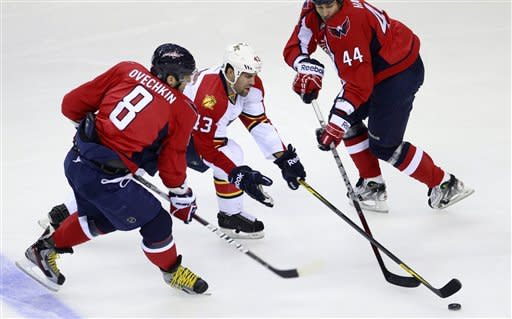 Florida Panthers defenseman Mike Weaver, center, squeezes between Washington Capitals left wing Alex Ovechkin, left, of Russia, and defenseman Roman Hamrlik (44), of the Czech Republic, during the first of an NHL hockey game Tuesday, Feb. 7, 2012, in Washington. (AP Photo/Haraz Ghanbari)