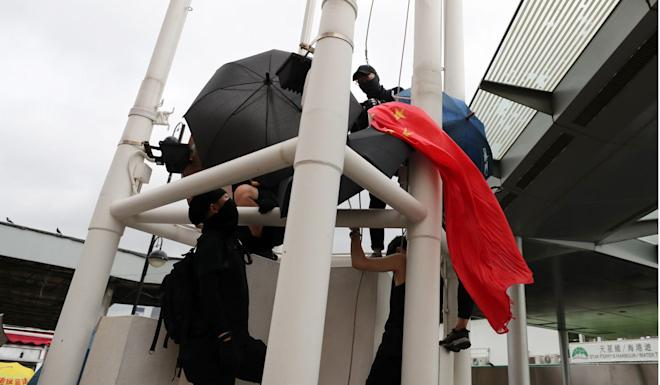 Protesters remove the national flag from a flagpole in Tsim Sha Tsui. Photo: Sam Tsang