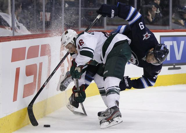 Winnipeg Jets' Evander Kane (9) gets dumped in Minnesota Wild's territory by Jared Spurgeon (46) during second-period NHL hockey game action in Winnipeg, Manitoba, Friday, Dec. 27, 2013. (AP Photo/The Canadian Press, John Woods)