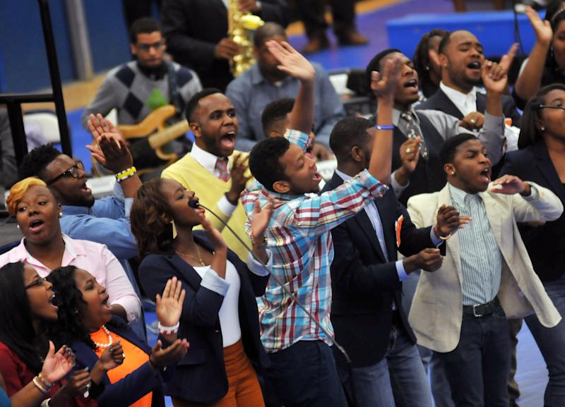 """Members of the Gospel Chorale sing at Virginia State University in Chesterfield County, Va. Friday, April 26, 2013 during a memorial service for two students, Jauwan Holmes and Marvell Edmondson, who drowned in the nearby Appomattox River on April 20. Edmonson of Portsmouth and Holmes of Newport News were swept away by the rapids of the Appomattox during what police have described as part of an initiation involving the group """"Men of Honor."""" Four men affiliated with the group have been charged with hazing. VSU has said the little-known group is not sanctioned by VSU. (AP Photo/The Progress-Index, Patrick Kane)"""