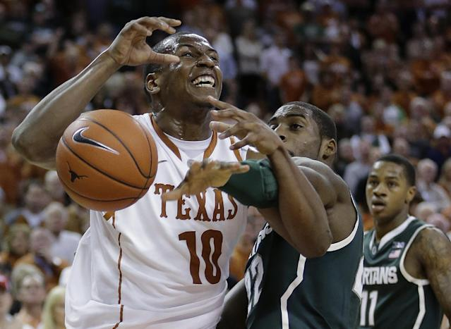 Texas' Jonathan Holmes (10) is fouled by Michigan State's Branden Dawson (22) during the first half of an NCAA college basketball game, Saturday, Dec. 21, 2013, in Austin, Texas. (AP Photo/Eric Gay)