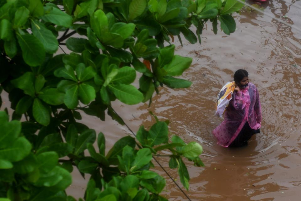 A resident wades along a waterlogged road after heavy rains following Cyclone Nivar landfall in Puducherry on November 26, 2020. (Photo by ARUN SANKAR/AFP via Getty Images)