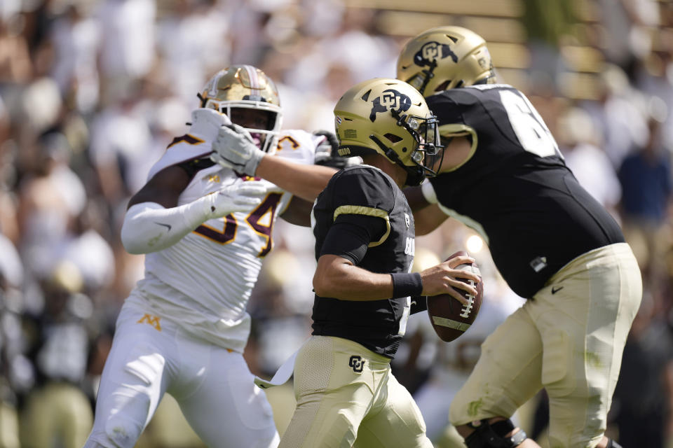 Colorado quarterback Drew Carter, front, runs for a short gain as offensive lineman Gerad Christian-Lichtenhan, back right, tangles with Minnesota defensive lineman Boye Mafe in the second half of an NCAA college football game Saturday, Sept. 18, 2021, in Boulder, Colo. Minnesota won 30-0. (AP Photo/David Zalubowski)