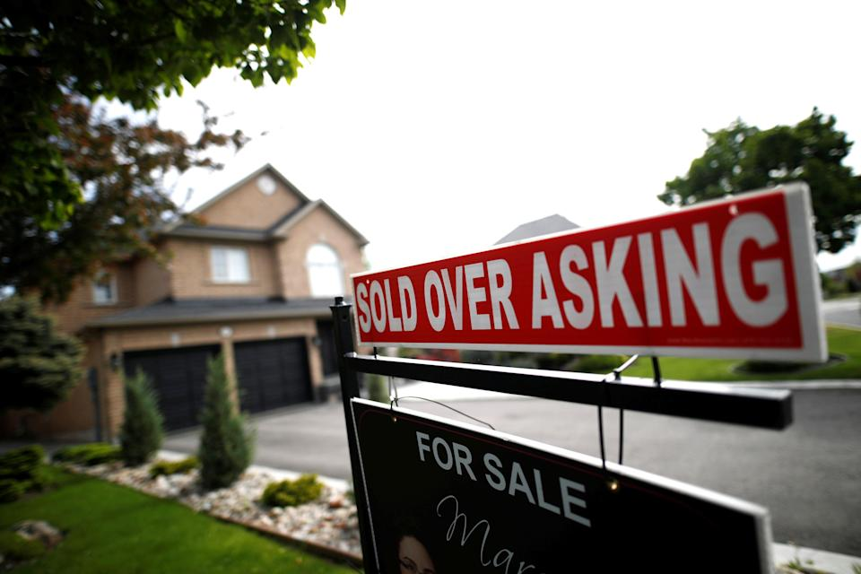 """A real estate sign that reads """"For Sale"""" and """"Sold Above Asking"""" stands in front of housing in Vaughan, a suburb in Toronto, Canada, May 24, 2017. (REUTERS/Mark Blinch)"""