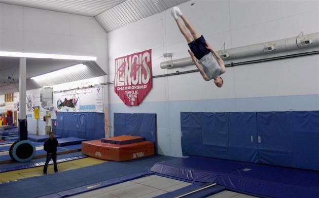 U.S. trampoline gymnast Michael Devine trains for the London 2012 Olympics at his home gym, the J and J Tumbling and Trampoline Team Center, while his coach Shaun Kempton (L) looks on in Pecatonica, Illinois, May 7, 2012.
