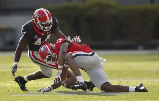 Georgia running back Elijah Holyfield (13) can't hang on to a pass as Juwan Taylor (44) defends during the second half of Georgia's annual G-Day spring football game Saturday, April 21, 2018, in Athens, Ga. (AP Photo/John Bazemore)