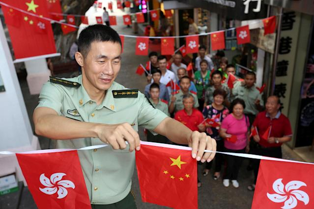 <p>A Chinese paramilitary policeman arranges Chinese and Hong Kong flags during an event marking the 20th anniversary of Hong Kong's handover from British to Chinese rule, on Chung Ying Street in Shenzhen, at the border with Hong Kong, Guangdong province, China, June 30, 2017. (Photo: Stringer/Reuters) </p>