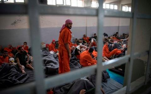 Men, allegedly affiliated with the Islamic State group, sit on the floor in a prison in the northeastern Syrian city of Hasakeh - Credit: AFP