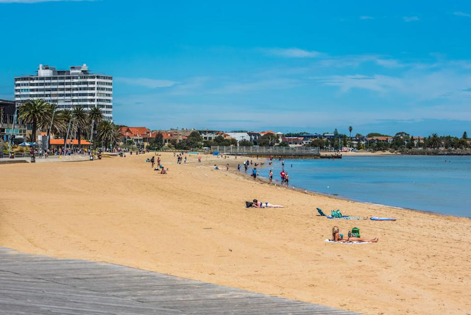 People sit on the sand at St Kilda beach on a sunny day.