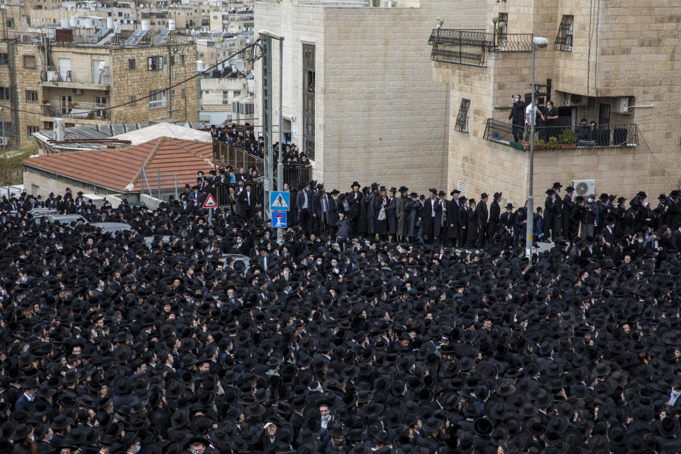 Thousands of ultra-Orthodox Jews participate in the funeral for prominent rabbi Meshulam Soloveitchik, in Jerusalem, Sunday, Jan. 31, 2021. The mass ceremony took place despite the country's health regulations banning large public gatherings, during a nationwide lockdown to curb the spread of the virus. (AP Photo/Ariel Schalit)