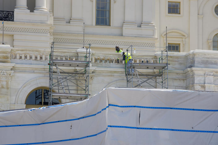 Workers on the West Front of the U.S. Capitol on Friday, Aug. 7, 2020, in Washington. While much of Washington is twisted in knots over the upcoming election, there's another contingent already busy trying to figure out how to stage an inauguration for the next president during a pandemic. (AP Photo/Jon Elswick)