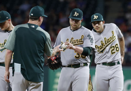 Oakland Athletics manager Bob Melvin (6) takes the ball from starting pitcher Brett Anderson (30) in the seventh inning of the team's baseball game against the Texas Rangers, as first baseman Matt Olson (28) stands by on the mound in Arlington, Texas, Friday, June 7, 2019. (AP Photo/Tony Gutierrez)