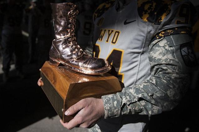 Spencer Jones, of the University of Wyoming ROTC, prepares to take the Bronze Boot to the field as Wyoming faced Colorado State in an NCAA college football game Saturday, Oct. 19, 2013, at War Memorial Stadium in Laramie, Wyo. (AP Photo/Casper Star-Tribune, Ryan Dorgan)