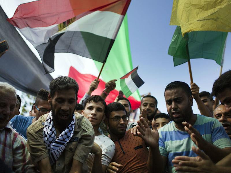 Palestinians wave National and Egyptian flags as they celebrate the reconciliation agreement between Hamas and Fatah in Gaza City: AP
