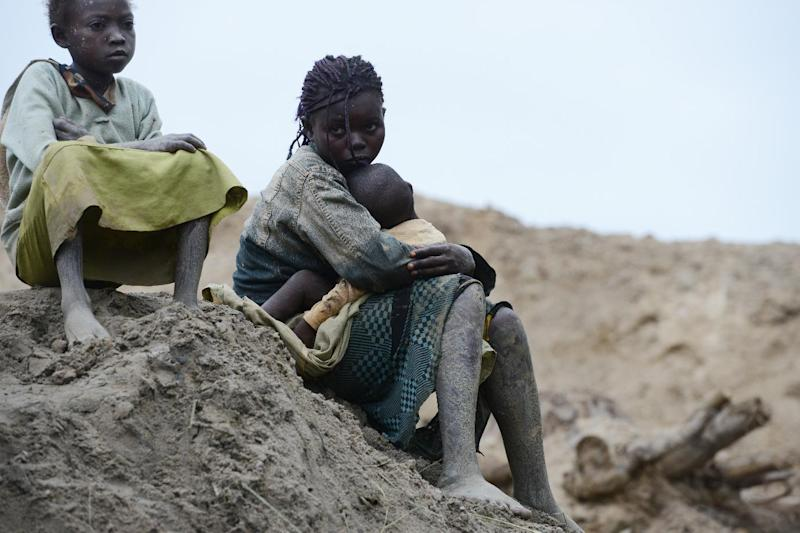 Children gold miners sit on May 5, 2014 next to a traditional mine in the village of Gam where gold mining is the main business activity