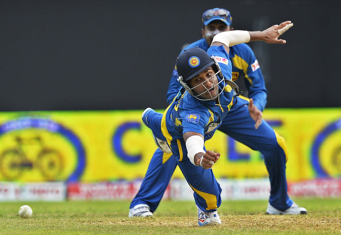Sri Lankan cricketer Dinesh Chandimal (front) dives to field a ball during the third match of the Tri-Nation series between India and Sri Lanka at the Sabina Park stadium in Kingston on July 2, 2013. Sri Lanka have scored 348/1 at the end of their innings. AFP PHOTO/Jewel Samad