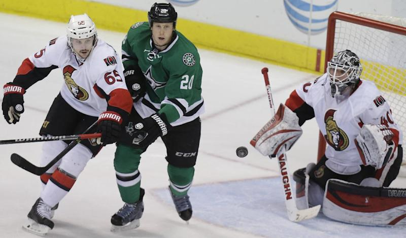 Dallas Stars center Cody Eakin (20) and Ottawa Senators defenseman Erik Karlsson (65) position themselves in front of goalie Robin Lehner (40) as the puck flies in during the second period an NHL Hockey game Saturday, March 22, 2014, in Dallas. (AP Photo/LM Otero)