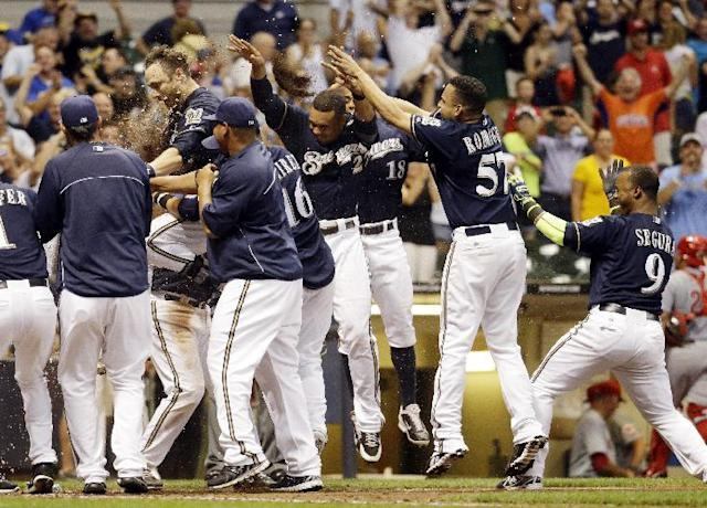 Milwaukee Brewers' Jonathan Lucroy celebrates with teammates after hitting a walk off home run during the ninth inning of a baseball game against the Cincinnati Reds Tuesday, July 22, 2014, in Milwaukee. The Brewers won 4-3. (AP Photo/Morry Gash)