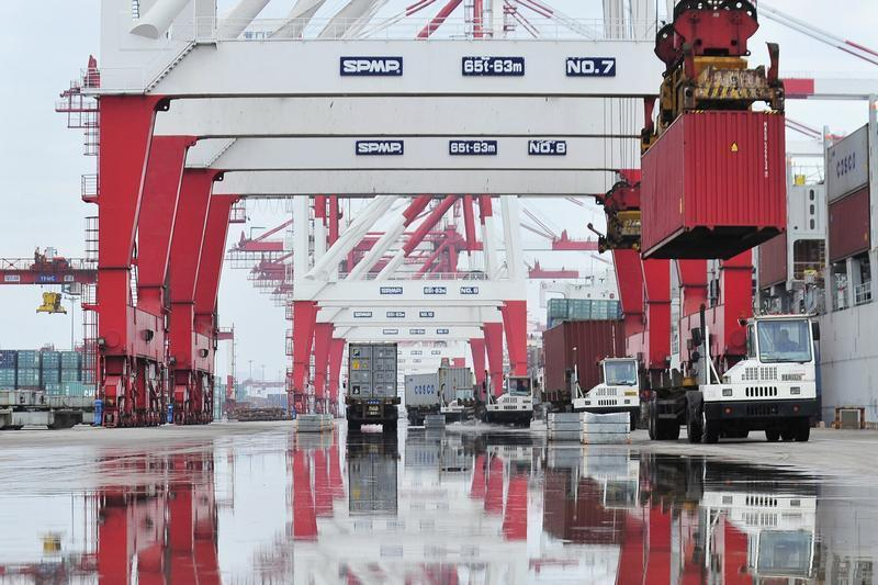Trucks are loaded with shipping containers at a port in Yingkou
