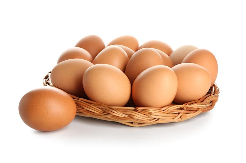 Wicker tray with raw brown chicken eggs on white background