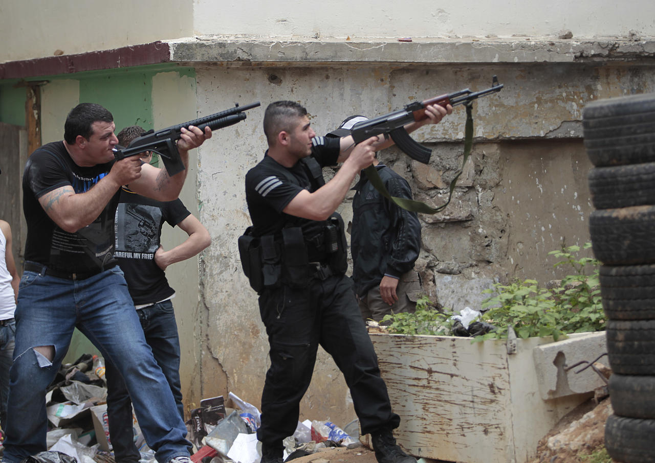 Sunni gunmen fire their rifles during clashes, in the northern port city of Tripoli, Lebanon, Sunday May 13, 2012. Gunfire broke out in the city Saturday and continued through the night primarily between a neighborhood populated by Sunni Muslims who hate Syrian President Bashar Assad and another area with many Assad backers from his Alawite sect. Lebanon's national news agency NNA said one soldier was shot dead by a sniper in the city early Sunday. Another man was found dead on the side of a road while a third died after a shell landed in a residential neighborhood. (AP Photo/Hussein Malla)
