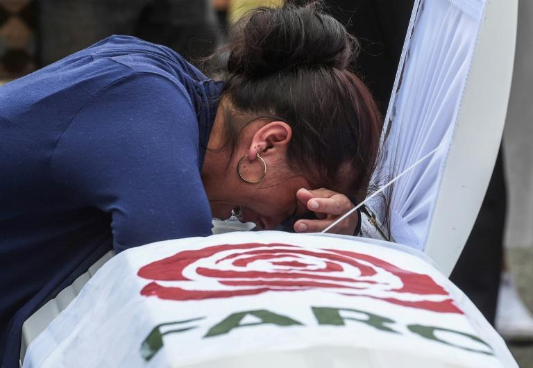 A relative mourns over the coffin of former FARC guerrilla Manuel Antonio Gonzalez on December 17, 2019, in Medellin, near the end of the deadliest year for the former Colombian rebels since a 2016 peace deal