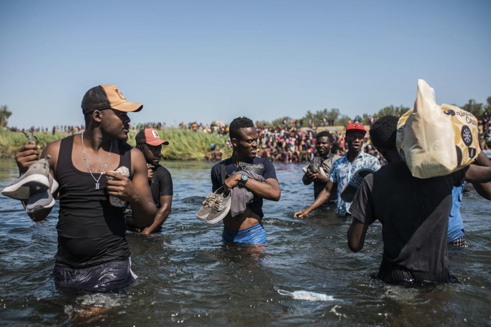 Migrants wade back and forth across the Rio Grande from Ciudad Acuña, Mexico, into Del Rio, Texas, Sunday, Sept. 19, 2021. Thousands of Haitian migrants have been arriving to Del Rio, Texas, as authorities attempt to close the border to stop the flow of migrants. (AP Photo/Felix Marquez)