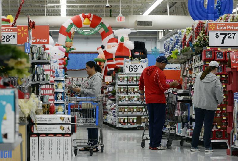 Customers shop for Christmas ornaments at a Walmart store in the Porter Ranch section of Los Angeles in this November 26, 2013, file photo. With growing online competition, no fashion must-haves and weak consumer confidence, most U.S. retailers will have to offer both big discounts and stellar service to get consumers to spend freely, according to retail analysts who joined Reuters reporters on visits to stores in New York, New Jersey, California and Illinois ahead of the holiday season. REUTERS/Kevork Djansezian/Files (UNITED STATES - Tags: BUSINESS ANNIVERSARY)