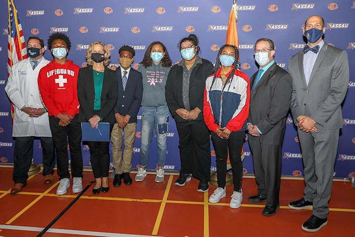 The Nassau County youth vaccine ambassadors, accompanied by, left to right, Dr. Daniel Fagan of Northwell Health, Nassau County Executive Laura Curran, Nassau County Commissioner of Health Lawrence Eisenstein and Dr. Jermaine Williams, President of Nassau Community College. Nicolette Carrion stands center in grey hoodie. (Office of the Nassau County Executive)