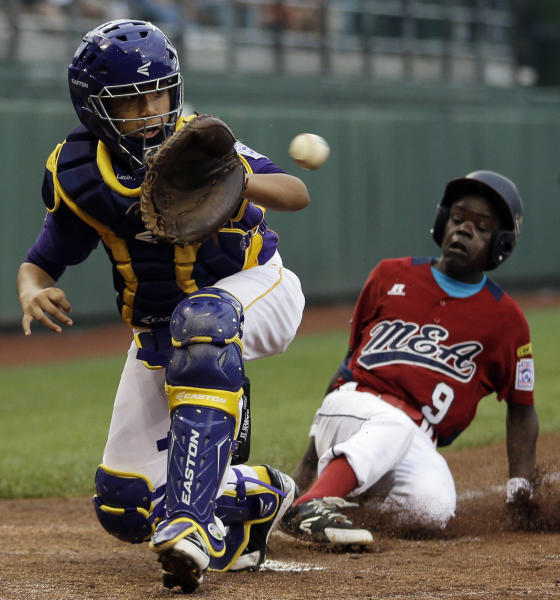 Lugazi, Uganda's Felix Enzama, right, scores past Aguadulce, Panama's Juan Crisp after a wild throw on a pickoff attempt to first base in the third inning of a pool play baseball game at the Little League World Series, Friday, Aug. 17, 2012, in South Williamsport, Pa. Panama won 9-3. (AP Photo/Matt Slocum)