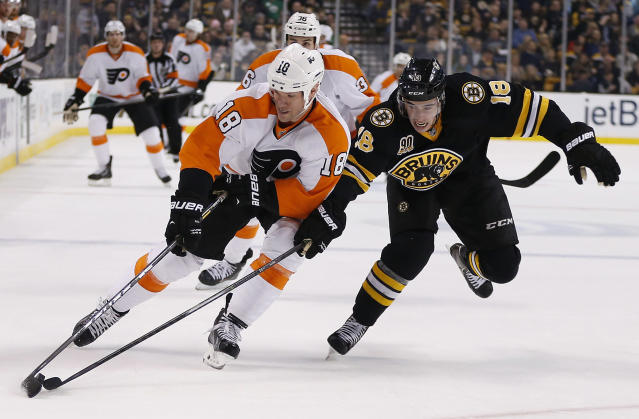 Philadelphia Flyers' Adam Hall, left, and Boston Bruins' Reilly Smith battle for the puck in the first period of an NHL hockey game in Boston, Saturday, April 5, 2014. (AP Photo/Michael Dwyer)
