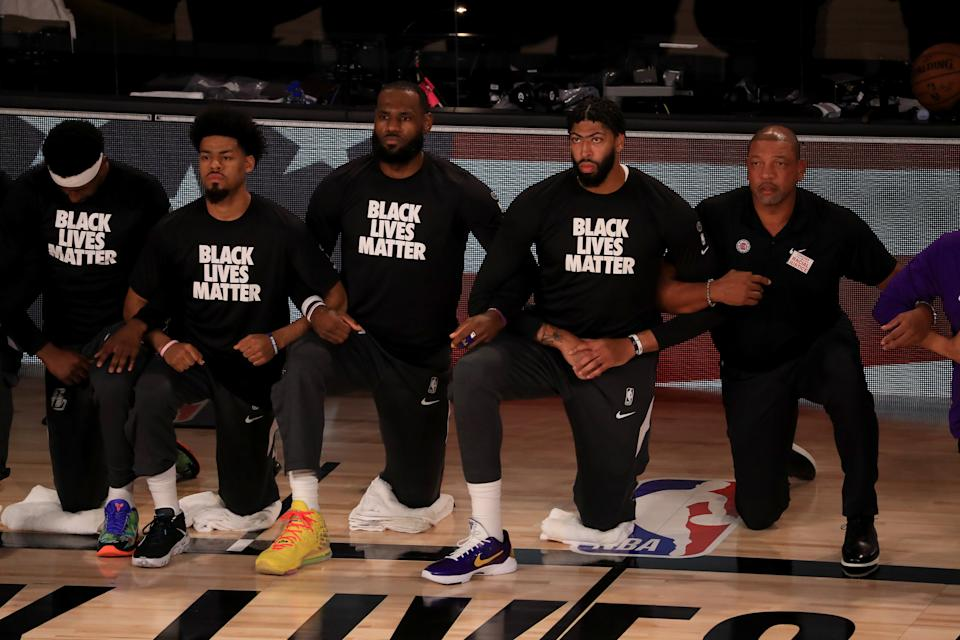 LeBron James #23 and Anthony Davis #3 of the Los Angeles Lakers in a Black Lives Matter Shirt kneel with their teammates during the national anthem.