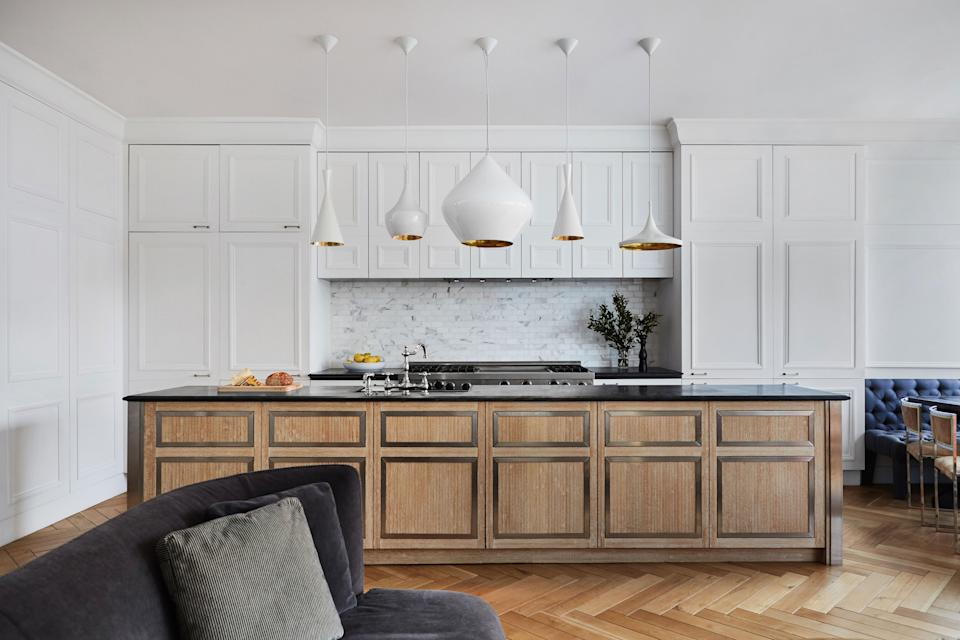 """The cabinetry and all the walls have the same molding in order to convey a sense of continuity throughout the apartment. The herringbone floors and chalky white paint make Blinken """"feel like I'm in Paris."""" The focal point of the kitchen is the array of Tom Dixon lights."""