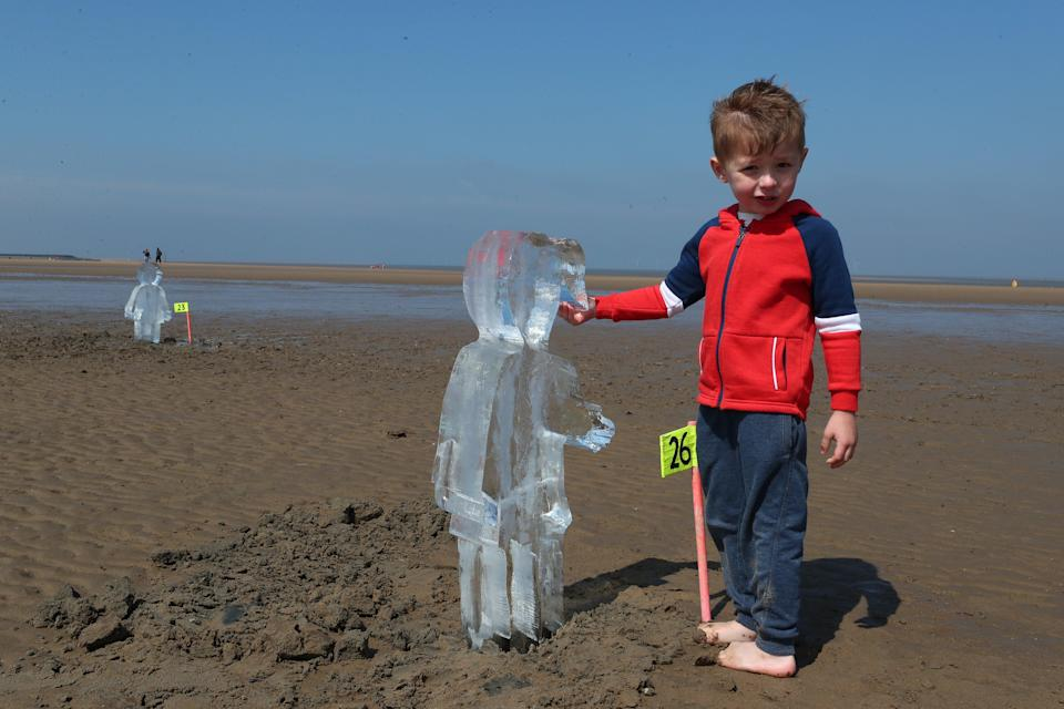 <p>Toby Heptinstall, three, looks at one of 26 ice sculptures of children installed on New Brighton Beach, Wallasey in Merseyside</p> (PA Wire)