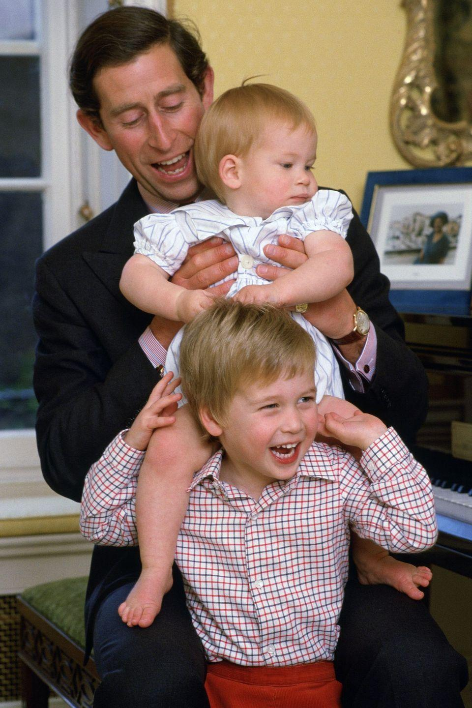 <p>The royal couple welcomed Prince William in 1982 and Prince Harry in 1984. Here, Charles, the Prince of Wales, has a silly moment with his two sons at home in Kensington Palace.</p>
