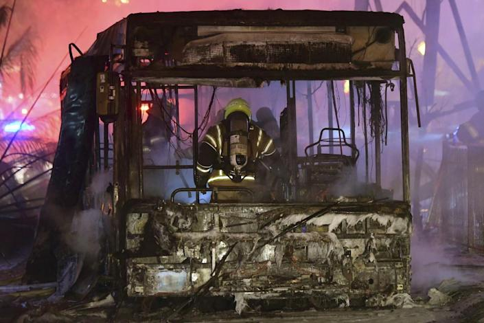 A firefighter stand in the scorched wreckage of a bus