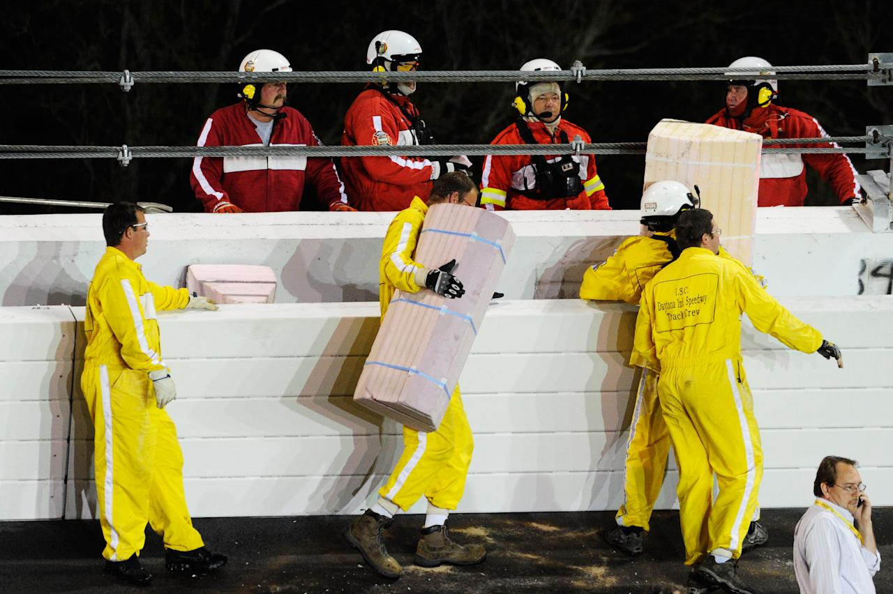 DAYTONA BEACH, FL - FEBRUARY 27: Safety workers replace foam blocks in the safer barrier after a jet dryer burst into flames after being hit under caution by Juan Pablo Montoya, driver of the #42 Target Chevrolet, during the NASCAR Sprint Cup Series Daytona 500 at Daytona International Speedway on February 27, 2012 in Daytona Beach, Florida.  (Photo by John Harrelson/Getty Images for NASCAR)