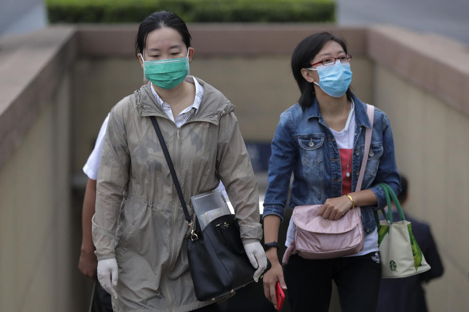 Women wearing face masks to help curb the spread of the coronavirus walk out from a subway station in Beijing, Tuesday, Sept. 15, 2020. Even as China has largely controlled the outbreak, the coronavirus is still surging across other parts of the world. (AP Photo/Andy Wong)