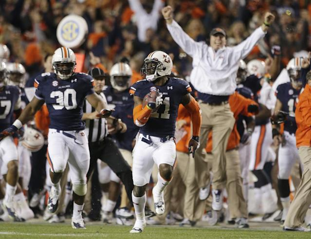 FILE - In this Nov. 30, 2013 file photo, Auburn cornerback Chris Davis (11) returns a field goal attempt 109-yards to score the winning touchdown over Alabama during the second half of an NCAA college football game in Auburn, Ala. Davis's 109-yard return of a missed field goal to beat Alabama was one of the Iron Bowl's and the season's most memorable plays. (AP Photo/Dave Martin, File)