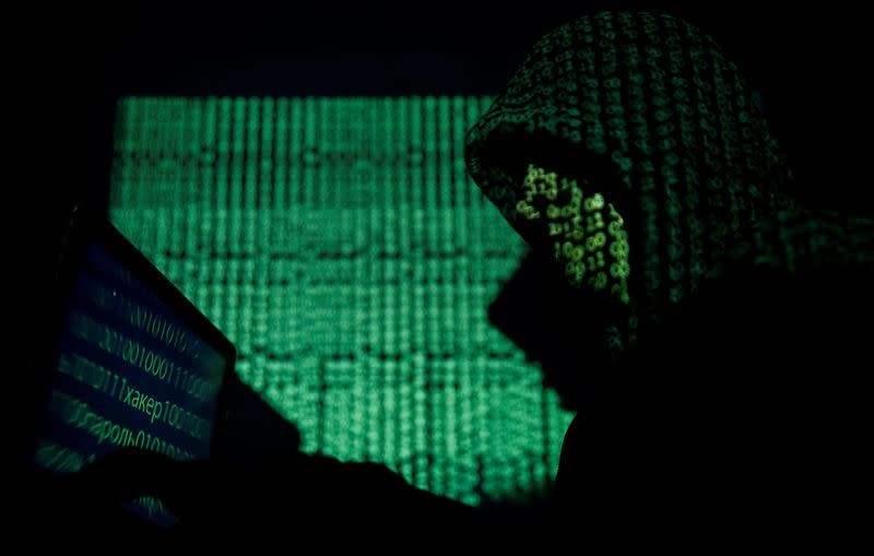 FILE PHOTO: Hooded man holds a laptop computer as cyber code is projected on him in this illustration picture