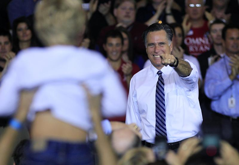 Republican presidential candidate, former Massachusetts Gov. Mitt Romney points to a young boy being held up by a supporters during a campaign rally at Jet Machine, Thursday, Oct. 25, 2012, in Cincinnati. The company is a defense contractor. (AP Photo/Al Behrman)