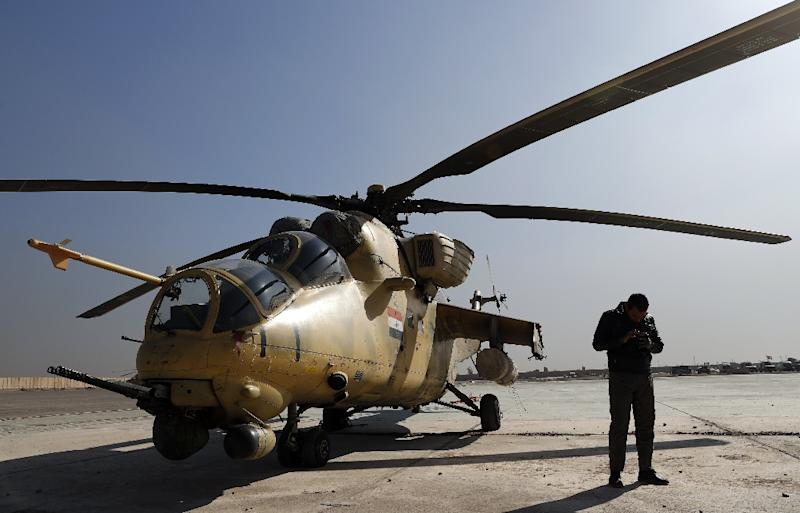 Iraqi soldiers perform maintenance on an airforce MI-35 helicopter at the army base of Qaryat Jaddalat, south of the city of Mosul on November 25, 2016 (AFP Photo/Thomas Coex)