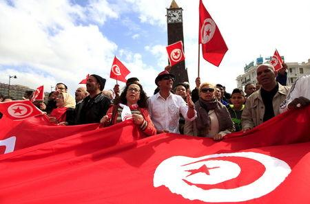 Tunisian protesters shout slogans as they wave banners and their national flag during a demonstration on Bourguiba Avenue capital of Tunis
