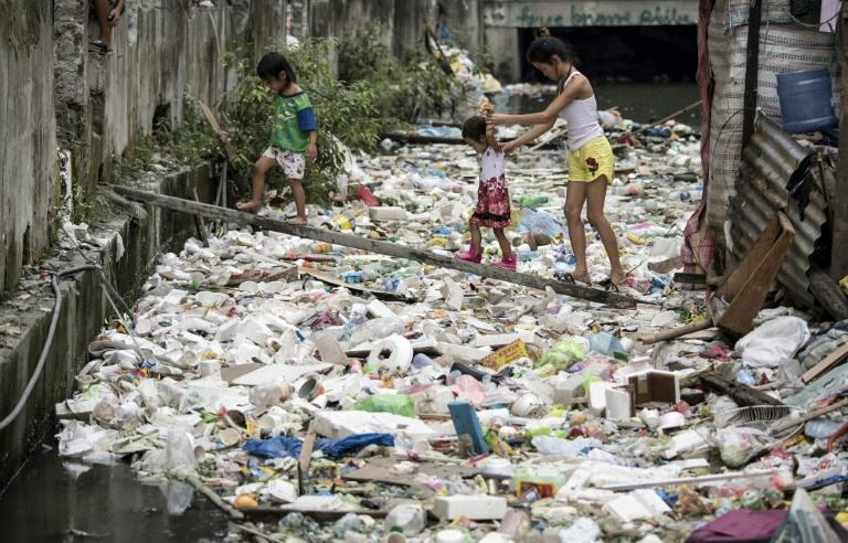 Residents walk on a wooden plank to cross a garbage-filled waterway in Manila on January 17, 2018