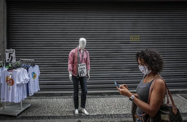 RIO DE JANEIRO, BRAZIL - JUNE 27: A woman wearing a face mask walks at the Saara commercial center amidst the coronavirus (COVID-19) pandemic on June 27, 2020 in Rio de Janeiro, Brazil. Some stores have not yet resumed activity or went bankrupt due to the pandemic. Mayor Marcelo Crivella moved forward the reopening of street commerce in Rio de Janeiro. The establishments are authorized to operate between 11 AM and 5 PM. According to the mayor, the reopening was approved by the city council's scientific committee. (Photo by Andre Coelho/Getty Images)