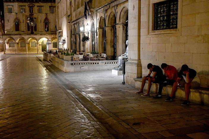 Image: Three youths looking at their mobile phones on empty street in the old town of the southern Croatian city of Dubrovnik, as the country eases lockdown measures taken to curb the spread of the COVID-19 pandemic (Denis Lovrovic / AFP - Getty Images)