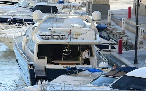 Maltese police on board Fenech's yacht after it was intercepted at sea by the Maltese military - Credit: AP