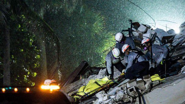 PHOTO: Search and Rescue personnel pull a body out of the rubble after the partial collapse of the Champlain Towers South in Surfside, north of Miami Beach, on June 24, 2021. (Chandan Khanna/AFP via Getty Images)