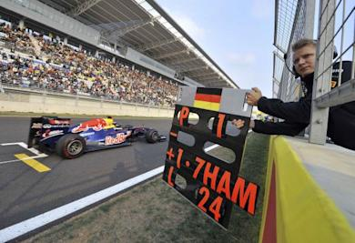 A Red Bull Formula One team member holds out an information board for driver Vettel of Germany as he passes the grid during the South Korean F1 Grand